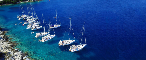 Aerial drone ultra wide photo of sail boats docked in paradise bay of Fiskardo, Kefalonia island, Ionian, Greece