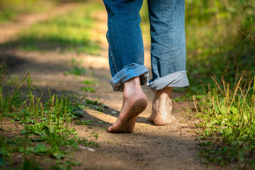 Man walking in park. Close-up of bare feet soiled with ground. healthy lifestyle.