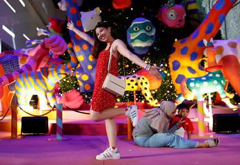 A woman poses for photo as she celebrates Christmas in Bangkok