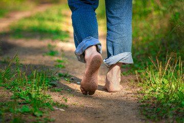Man walking on footpath forest. Close-up of bare feet soiled with ground. healthy lifestyle.