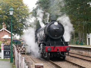 old steam locomotive train with steam billowing around and onto tracks