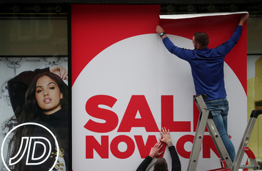 Workers hang a 'sale' sign on the front of a shop in London