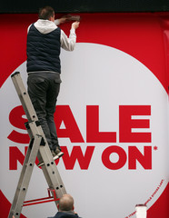 A worker hangs a 'sale' sign on the front of a shop in London