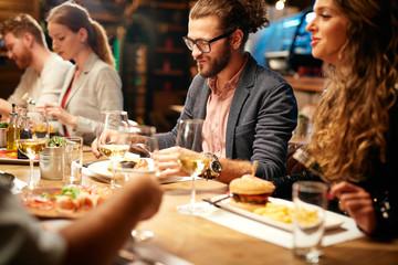 Group of best friends sitting in restaurant, having dinner, drinking wine and having fun.