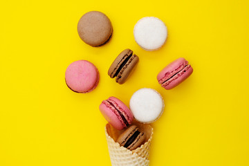 Foto auf AluDibond Macarons Macarons cakes. Stil life photo of waffle cone with macaroons on yellow background. Flat lay, dessert.