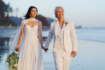 Attractive lesbian couple on the sandy seashore in the sunset rays, happily smiling, dressed in wedding clothes