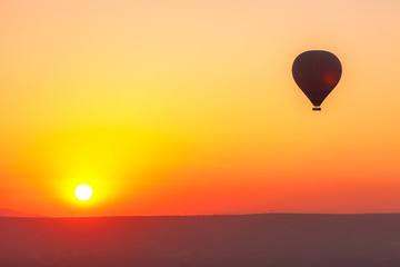 Fototapeten Gelb Many colorful balloons fly over the mountains - a panorama of Cappadocia at dawn. Goreme Valley Landscape in Cappadocia - Background for your travel concept in Turkey.