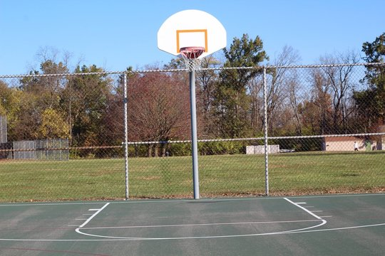 The basketball hoop court in the park on a sunny day.