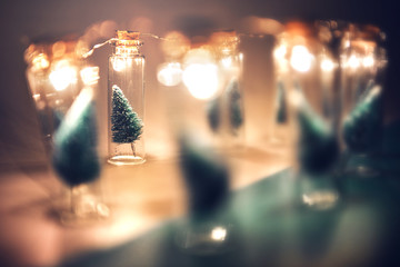 Fototapete - Close-up, Elegant Christmas tree in glass jar on green color background. copy space.