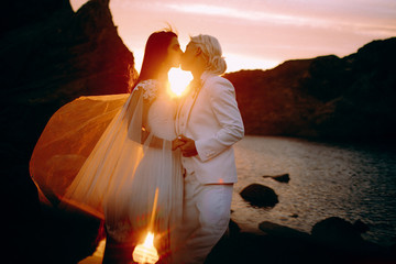 Lesbian couple is passionately kissing on picturesque landscape with beautiful sunset