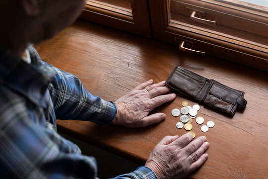 Hands of an old man and counting money, coins. The concept of poverty, low income, austerity in old age.