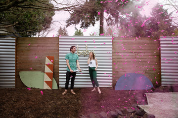 A young married couple celebrate the gender of their baby at a gender reveal party