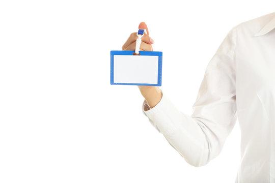 Female hand holding blank bagde on white background