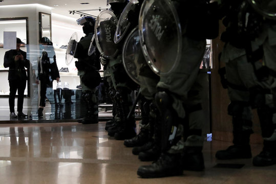 Riot police stand guard inside a shopping mall during an anti-government protest on Christmas Eve at Tsim Sha Tsui in Hong Kong