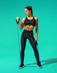 Strong woman working with resistance band. Photo of attractive woman in black sportswear on turquoise background. Strength and motivation