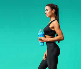 Sporty girl holds shaker with protein cocktail. Photo of attractive girl in black sportswear on turquoise background.  Sports and healthy lifestyle