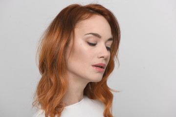 the face of a beautiful woman in half a turn is the so-called 2/3 or 3/4 turn, her mouth is ajar, red hair, on a neutral background, space for text