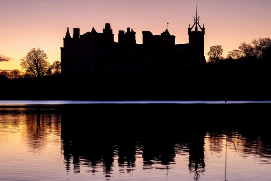 Silhouette of an old castle on the lake against the backdrop of the rising sun. Linlithgow Palace, Scotland