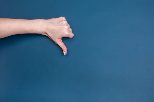 Female hand shows thumb down on blue background, place for text
