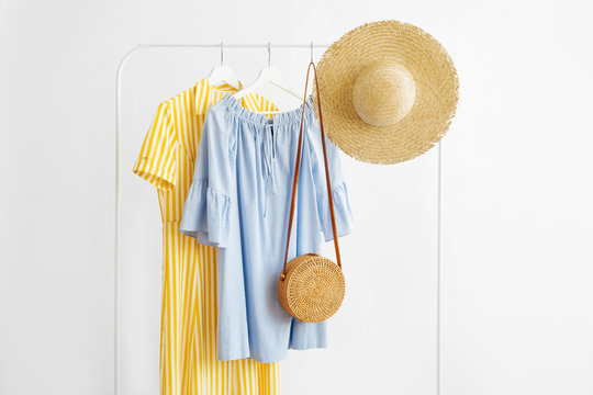 Summer dresses and straw hat with bamboo bag on hanger on white background. Elegant   fashion outfit. Spring wardrobe. Minimal concept.