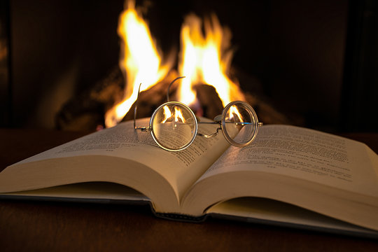 close up of vintage eyeglasses on open book with fireplace background