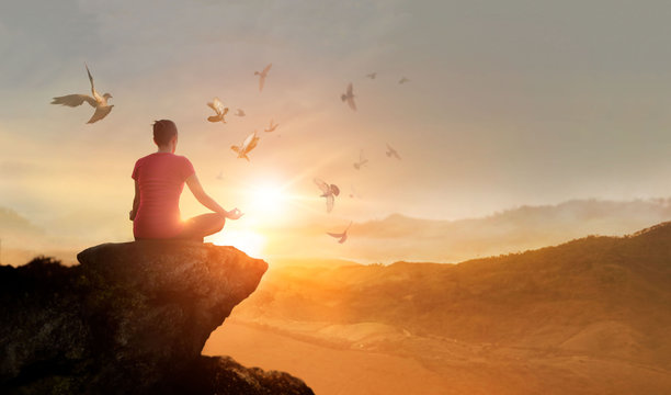 Woman practices meditating and praying with free bird enjoying nature on the mountain sunset background, hope and faith concept.