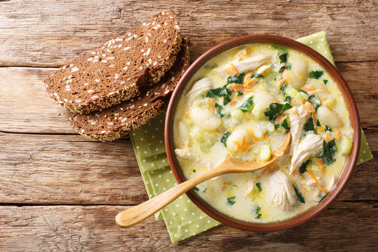 Homemade Italian cream soup with gnocchi, chicken and spinach served with bread close-up in a bowl. Horizontal top view
