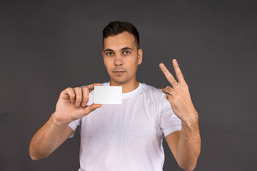 A young man in a white t-shirt holds a business card