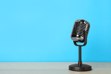 Papiers peints Nature Retro microphone on wooden table against light blue background, space for text. Interview