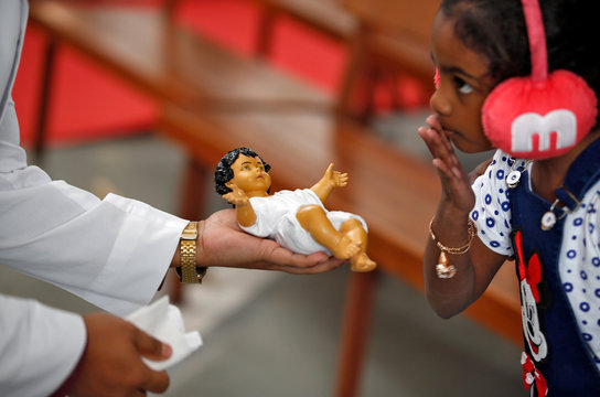 A girl kisses a figure of the baby Jesus at a church during Christmas celebrations in Ahmedabad