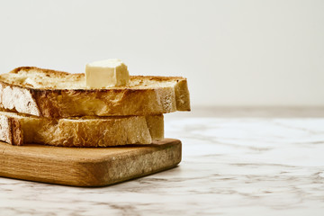 Fototapeten Brot Slices of fried freshly baked bread with a piece of butter on top, lie on a wooden shelf on a marble table