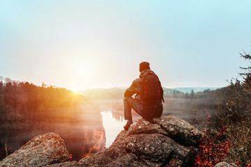 Foto auf AluDibond Entspannung Young man in jacket, pants and backpack sitting on rock looking to river Vltava and valley in sunset.