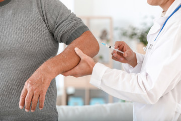 Doctor giving mature man with joint pain injection at home, closeup