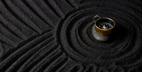 Photo sur Plexiglas Zen pierres a sable golden compass on black stones in dark sand background