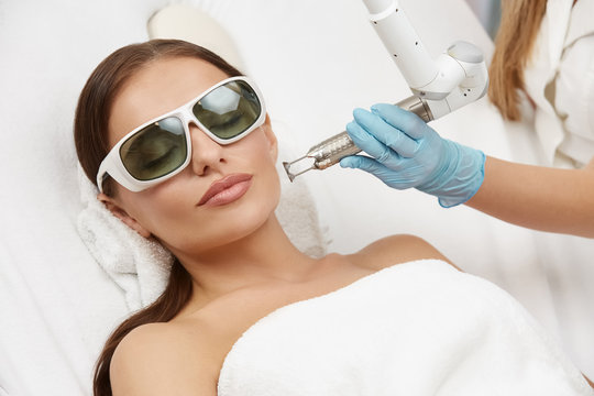 beautician wearing gloves and holding laser near beautiful woman lying with protection glasses in beauty salon