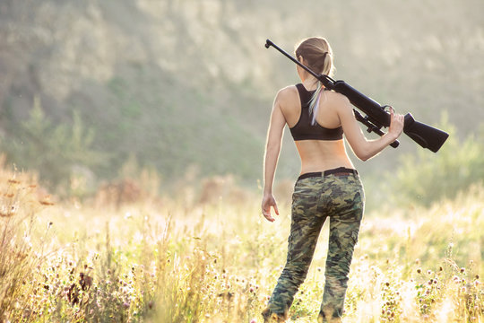 Back view sexy military fashion girl with rifle with an optical sight. Female chase sport hunter in forest with weapon.