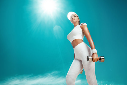 Sporty and fit woman athlete doing training with dumbbells on the sky background. The concept of a healthy lifestyle and sport. Individual sports recreation.