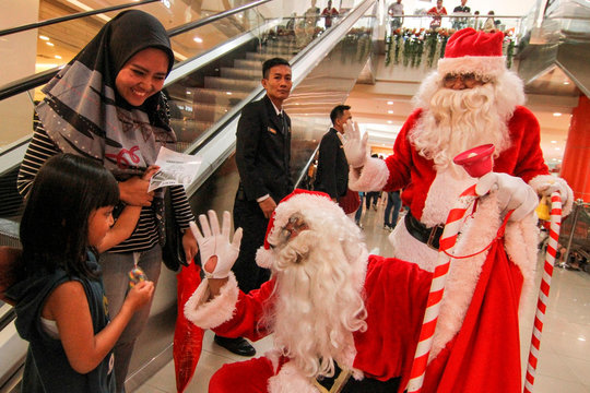 Men wearing Santa Claus clothes greet people and distribute sweets during Christmas holiday at a shopping mall in Depok, south of Jakarta