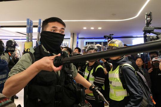 A riot police officer confronts Hong Kong protesters during a Christmas Day rally in Sha Tin shopping mall in Hong Kong