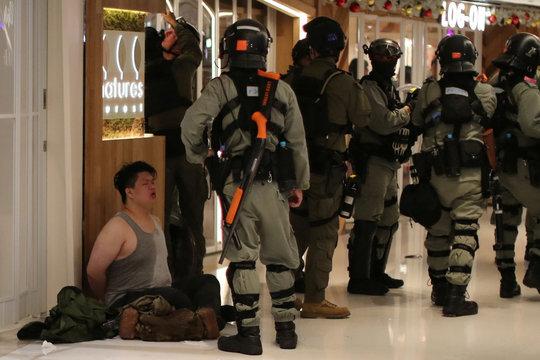 Riot police detain a Hong Kong protester during a Christmas Day rally in Sha Tin shopping mall in Hong Kong