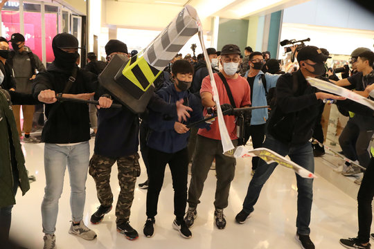 Hong Kong protesters throw a cone at plainclothes police officers during a Christmas Day rally in Sha Tin shopping mall in Hong Kong