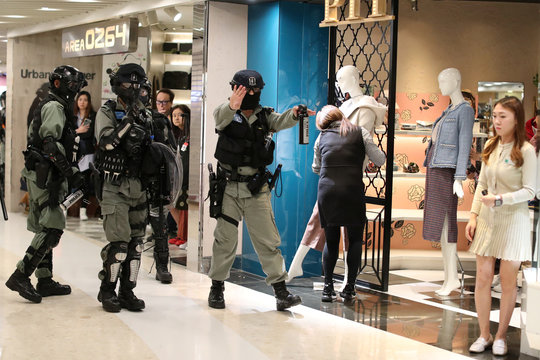 Riot police hold back Hong Kong protesters as a store worker rushes to take in a mannequin during a Christmas Day rally in Sha Tin shopping mall in Hong Kong