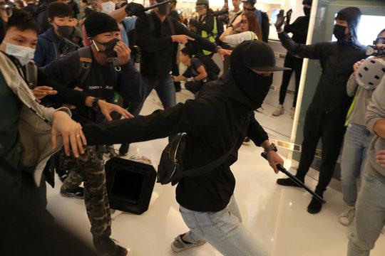 Plainclothes police officers charge Hong Kong protesters at a Christmas Day rally in Sha Tin shopping mall in Hong Kong