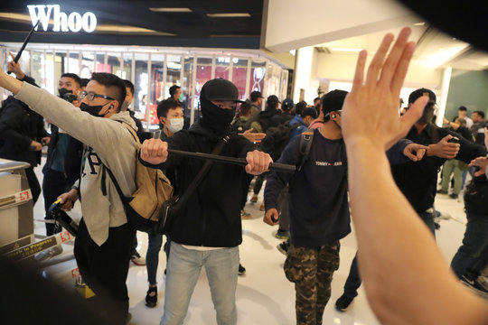Plainclothes police officers confront Hong Kong protesters during a Christmas Day rally in Sha Tin shopping mall in Hong Kong