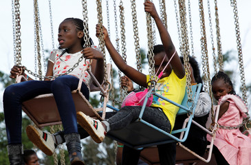 Revellers ride on a merry-go-round at the Uhuru Park grounds during Christmas Day celebrations in Nairobi