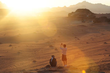 Jordan, Wadi Rum desert - tourists take pictures and looking the sunset during a travel