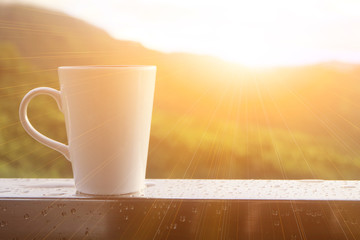 A white cup of coffee is on a balcony in the morning after rained, with mountain view and light of sun shine. Begining day concept.