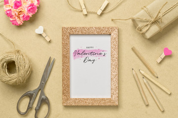 Mockup photo frame with kraft present boxes and craft rose flower for Valentines day concept. Top view of mock up photo frame with craft decoration and on wood background. top view with copy space. Wall mural