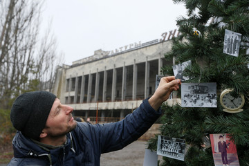 A former resident of Pripyat decorates a Christmas tree in Pripyat