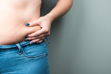 A plump woman in jeans, a fold of skin in her hand. The concept of losing weight by summer